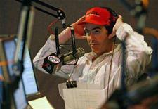 <p>Radio host Adam Carolla takes off his head phones during a commercial break during the Adam Carolla morning radio show at KLSX studios in Los Angeles, California, August 8, 2006. REUTERS/Danny Moloshok</p>