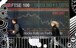 <p>Un uomo e una donna camminano davanti a un display elettronico coi grafici dell'andamento della Borsa, a Londra. REUTERS/Alessia Pierdomenico</p>