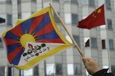 <p>Un uomo sventola la bandiera del Tibet durante una manifestazione davanti all'ambasciata cinese per protestare contro il comportamento della Cina. REUTERS/Tobias Schwarz (GERMANY)</p>