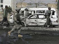 <p>A U.S. soldier walks past damaged vehicles at the site of a bomb attack in Kabul March 13, 2008. Afghan police backed by U.S. troops killed three Taliban fighters and captured three more in a 40-minute gunbattle in southern Afghanistan on Saturday, a Reuters witness said.. REUTERS/Omar Sobhani</p>