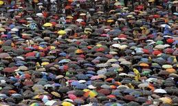 <p>Fedeli sotto l'ombrello stamattina a piazza San Pietro per la messa di Pasqua. REUTERS/Alessandro Bianchi</p>
