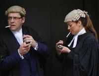 <p>Due avvocati fumano all'esterno del tribunale nel centro di Londra. REUTERS/Toby Melville</p>