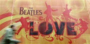 "<p>A pedestrian passes a large advertising display in west London for Beatles music compilation album ""Love"", December 29, 2006. REUTERS/Toby Melville</p>"