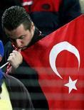 """<p>Турецкий болельщик держит в руках флаг своей страны на отборочном этапе чемпионата по футболу 2006 года 16 ноября 2005 года. Вооруженные мужчины застрелили главного тренера и тренера вратарей турецкого футбольного клуба """"Бафраспор"""", выступающего в третьем дивизионе, сообщил веб-сайт клуба во вторник. (REUTERS/Fatih Saribas )</p>"""