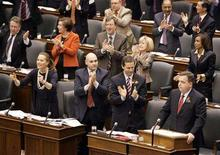 <p>Liberal Party members applaud Finance Minister Dwight Duncan (R) as Duncan tabled the 2008 Ontario provincial budget in Toronto March 25, 2008. REUTERS/ Mike Cassese</p>
