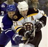 <p>Toronto Maple Leafs Darcy Tucker (L) hooks Boston Bruins Glen Murray for a penalty during second period action in their NHL game in Toronto March 25, 2008. REUTERS/Fred Thornhill</p>