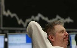 <p>Un operatore della borsa di Francoforte si stira in una pausa delle contrattazioni. Sullo sfondo il tabellone del Dax, il più importante indice azionario statunitense. REUTERS/Alex Grimm (GERMANY)</p>