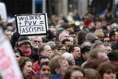 <p>A demonstrator holds a sign during a protest against Dutch politician and anti-Islam film-maker Geert Wilders at Dam square in Amsterdam March 22, 2008. REUTERS/Ade Johnson</p>