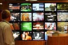 <p>Un visitatore in uno stand di televisori. REUTERS/Eric Gaillard</p>