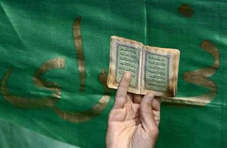 An Afghan man holds a small copy of some verses of the Koran during a protest in Kabul March 21, 2008. Muslim nations condemned on Friday a film by a Dutch lawmaker that accuses the Koran of inciting violence, as Dutch Muslim leaders urged restraint. REUTERS/Ahmad Masood