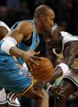 <p>Kevin Garnet, do Boston Celtics, tenta tirar a bola de jogador do Hornets. Photo by Brian Snyder</p>