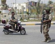 <p>A resident rides his scooter past an Iraqi soldier standing guard on a road in Basra March 31, 2008. REUTERS/Atef Hassan</p>