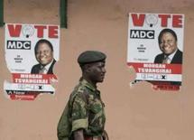 <p>Soldado do Zimbábue caminha em meio a cartazes do primeiro turno das eleições, no centro da capital Harare, em 2 de abril. Photo by Philimon Bulawayo</p>