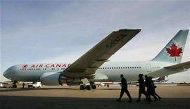 <p>An Air Canada flight crew walks past the newly unveiled aircraft colors at the Montreal headquarters on October 19, 2004. REUTERS/Christinne Muschi</p>