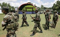 <p>Военные обходят место взрыва в районе Гампаха 6 апреля 2008 года. В результате взрыва, организованного смертником недалеко от столицы Шри-Ланки в воскресенье, погибли не менее 12 человек, включая министра дорожного хозяйства Джеяраджа Фернандопулле, и 100 получили ранения, сообщило правительство страны. (REUTERS/Anuruddha Lokuhapuarachchi)</p>