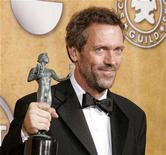 "<p>Actor Hugh Laurie holds his award for best male actor in drama series for his role in television show ""House"" at the 13th Annual Screen Actors Guild Awards in Los Angeles January 28, 2007. REUTERS/Lucy Nicholson</p>"