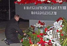 <p>Vladimir Putin lays flowers at the memorial near the Dubrovka theatre in southeast Moscow, October 23, 2003. REUTERS/Pool/Sergei Ilnitsky</p>