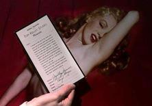 <p>An employee of Butterfields auction house displays a copy of a model release signed by Marilyn Monore in front of one of the photographs of Monroe during a Hollywood photo shoot in 1949, in Los Angeles, March 22, 2001. A 15-minute film of Marilyn Monroe engaging in an oral sex act with an unidentified man will be kept from public view by a New York businessman who has bought it for $1.5 million, the broker of the deal said on Monday. REUTERS/Fred Prouser</p>