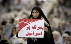 <p>Жительница Ирана держит антиизраильский плакат, Тегеран, 11 апреля 2008 года. Иран уничтожит Израиль, если Тель-Авив решит провести против Тегерана военную операцию, заявил во вторник один из высокопоставленных военачальников Исламской республики. REUTERS/Morteza Nikoubazl</p>