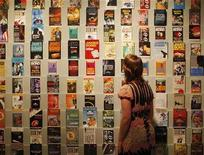 "<p>A woman looks at a collection of original 007 novels by Ian Fleming, at the ""For Your Eyes Only"" exhibition of Ian Fleming and James Bond memorabilia at the Imperial War Museum in London April 16, 2008. REUTERS/Stephen Hird</p>"