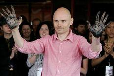 "<p>Billy Corgan, member of the rock group ""Smashing Pumpkins"", shows his hands covered with black cement to the audience as he and band member Jimmy Chamberlin were inducted into the Hollywood Rock Walk in Hollywood April 23, 2008. The Rock Walk honors artists who have made a significant impact to the growth of Rock 'n' Roll. REUTERS/Fred Prouser</p>"