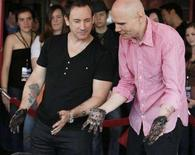 "<p>Due componenti della rock band ""Smashing Pumpkins"" Jimmy Chamberlin (sinistra) e Billy Corgan si guardano le mani ricoperte di cemento dopo aver lasciato oggi le loro impronte nella Hollywood Rock Walk di Hollywood. REUTERS/Fred Prouser (UNITED STATES)</p>"