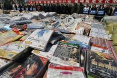 <p>Un stock de logiciels, DVD et CD contrefaits, en Chine. La police chinoise a saisi pour 750 millions de dollars de logiciels informatiques contrefaits et démantelé un réseau de pirates dans le sud de la Chine. /Photo d'archives/REUTERS/Claro Cortes IV (CHINA)</p>