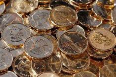 <p>Newly pressed Canadian one dollar coins at the Royal Canadian Mint in Winnipeg on November 14, 2007. REUTERS/Fred Greenslade</p>