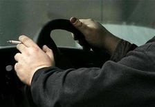 <p>A man holds a cigarette in his car in Toronto March 5, 2008. REUTERS/Mark Blinch</p>