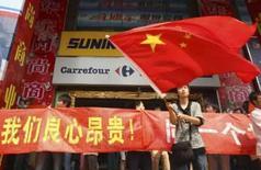 <p>Manifestante empunha bandeira chinesa em frente a um supermercado Carrefour em Chongqing, China, 1o de maio de 2008. Photo by Stringer Shanghai</p>