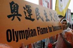 <p>Manifestante a favor da democracia carrega cartaz durante passagem da tocha olímpica por Hong Kong, em 2 de maio de 2008. Photo by Claro Cortes Iv</p>