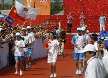 <p>A atleta chinesa e campeã olímpica Yang Yang (centro) corre com a tocha duranta passagem pela cidade de Sanya, na província de Hainan, dia 4 de maio, na China. Aplausos barulhentos e muita animação deram as boas vindas à tocha olímpica, neste domingo, na primeira parte de sua maratona pelo território chinês. Photo by China Daily</p>