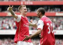 <p>Nicklas Bendtner (esq) do Arsenal comemora gol com Armand Traore durante partida neste domingo, dia 4 de maio, em Londres. O Everton perdeu a chance de confirmar um lugar na próxima temporada da Copa da Uefa ao perder por 1 x 0 para o Arsenal, neste domingo, no Campeonato Inglês. Photo by Stringer</p>