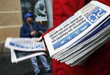 <p>Quotidiani gratuiti distribuiti all'ingresso di una fermata della metropolitana a Madrid, febbraio 2008. REUTERS/Susana Vera</p>