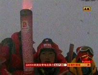 <p>A tocha olímpica é erguida no topo do monte Everest, em imagem de televisão, sia 8 de maio. Uma mulher tibetana deu os últimos passos para levar a tocha olímpica ao topo do monte Everest na quinta-feira, realizando 'um sonho de todo o povo chinês', mas grupos de defesa dos direitos humanos criticaram Pequim por politizar os Jogos. Photo by Reuters Tv</p>