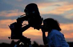 <p>Immagine d'archivio di una astronoma che usa un telescopio. REUTERS/Jeff Mitchell PP03080094 JM/SV</p>