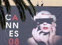 <p>Workers on the roof of the Festival Palace use ropes to position a giant canvas of the official poster of the 61st Cannes Film Festival in Cannes, May 12, 2008. Cannes film festival, the world's biggest, runs from May 14-25. REUTERS/Eric Gaillard</p>