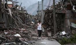 <p>Habitante de uma das regiões afetadas pelo terremoto anda entre os escombros na cidade de Hongbai.A China anunciou três dias de luto nacional a partir de segunda-feira, após o número de mortos pelo terremoto aumentar para quase 32.500 na última semana. Photo by Reinhard Krause</p>