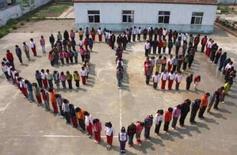 <p>Estudantes da província de Jiangsu formam um coração para homenagear as vítimas do terremoto no aniversário de uma semana da tragédia, em 19 de maio de 2008 . Photo by China Daily</p>