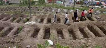 <p>Pessoas caminham entre túmulos vazios destinados às vítimas dos terremotos na China. O país elevou para mais de 70 mil o número oficial de mortos e desaparecidos pelo terremoto da semana passada. Photo by Carlf Zhang</p>
