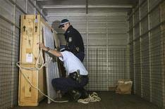 <p>Australian policemen load photographs onto a police truck after removing them from a gallery in Sydney May 23, 2008. REUTERS/Daniel Munoz</p>