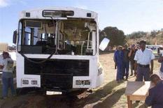 <p>Сотрудник полиции ЮАР у автобуса, попашего в аварию 1 мая 2003 года. Как минимум 30 человек погибли в результате крушения автобуса в Капской провинции на востоке ЮАР, сообщило информационное агентство SAPA во вторник. (REUTERS/Stringer)</p>