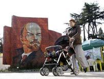 <p>Женщина везет коляску с ребенком на фоне мозаики с портретом Ленина в Сочи 9 апреля 2008 года. В Екатеринбурге судят женщину, которая продала свою четырехмесячную дочь за 20.000 рублей (REUTERS/Grigory Dukor)</p>