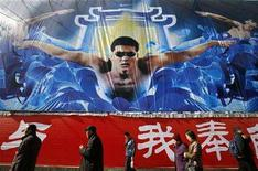 <p>Shoppers walk past an advertisement showing China's Olympic swimming hopeful Wu Peng at a shopping district in Beijing February 17, 2008. REUTERS/Claro Cortes IV</p>