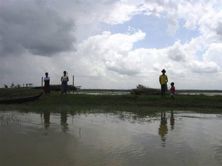 A family look for traces of their house, on a marooned embankment, in the village of Pay Kunhnasay in the Kawhmu township May 30, 2008. REUTERS/Aung Hla Tung