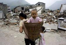 <p>Una madre porta il suo bambino sulle spalle mentre cammina nei pressi delle rovine di un edificio distrutto dal terremoto nella provincia del Sichuan. REUTERS/Jason Lee (CHINA)</p>