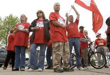 <p>General Motors employees hold signs outside its Canadian headquarters in Oshawa, Ontario June 4, 2008. Hundreds of angry autoworkers blockaded the entrance on Wednesday, demanding the company reverse its decision to close the local truck plant and crying foul over the timing of the closure. REUTERS/Fred Thornhill</p>