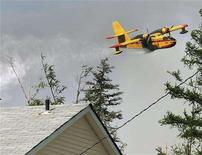 <p>A plane drops water over homes in Lake Echo, Nova Scotia, June 14, 2008. Residents have been evacuated after the forest fire, which began Friday, is continuing to burn out of control. REUTERS/Paul Darrow</p>