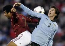 <p>O jogador uruguaio, Diego Godin (direita), divide a bola com o jogador venezuelano, Alexander Rondon, durante partida classificatória para a Copa de 2010 em Montevidéu. A seleção da Venezuela comemorou como um passo importante o empate de 1 x 1 diante do Uruguai. Photo by Andres Stapff</p>