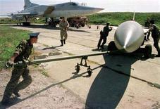 <p>Крылатую ракету подтягивают к самолету Ту-22 на военной базе около Уссурийска, 17 сентября 1999 года (архивная фотография). Российские власти решили отказаться от услуг украинских поставщиков двигателей для крылатых ракет, сообщил в понедельник гендиректор государственного НИИ авиационных материалов Евгений Каблов. (REUTERS/Str Old)</p>